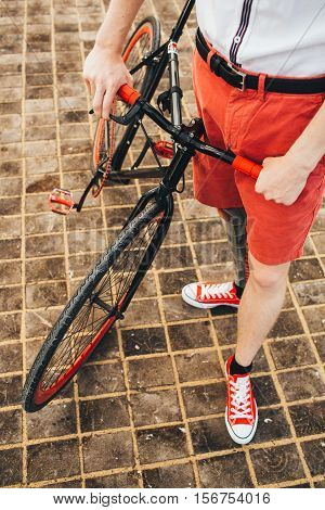 Hipster with red bycicle and tatoo at square floor