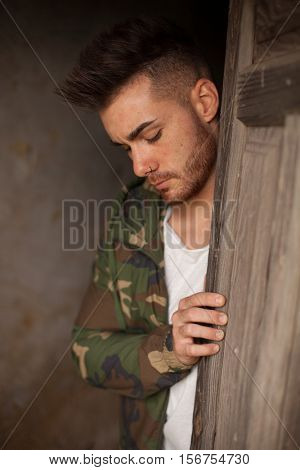 Atractive guy with jacket with military stylish in a vintage house