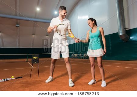 Hold it in such a way. Pleasant handsome professional instructor holding racket and teaching young beautiful slim woman to play tennis in indoor court