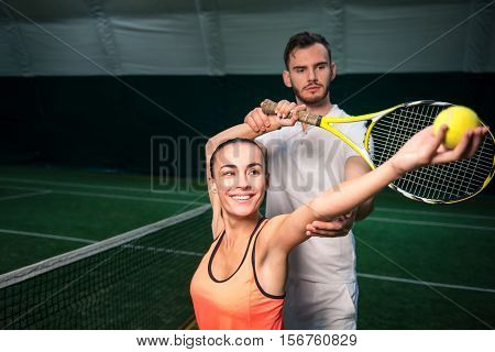 Engaged in process. Cheeful beautiful woman serving a ball while professional instructor controlling the process while training in an indoor court