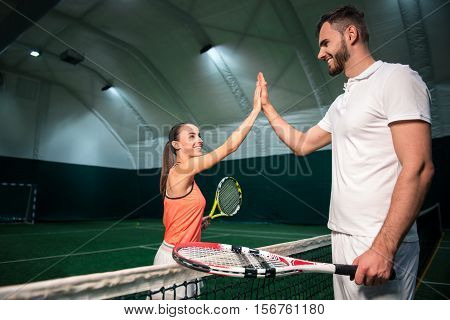 Who will be the winner. Positive smiling tennis players giving high five and standig near tenis net while going to start playing tennis