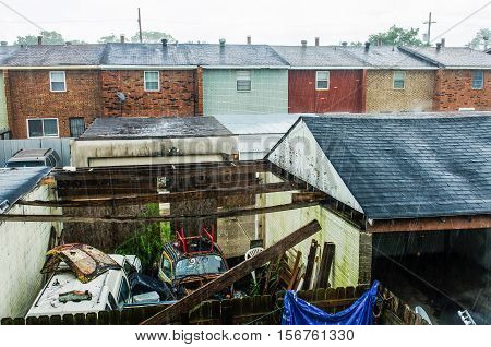 New Orleans, USA - July 8, 2015: Backyard of townhome during rain with junk