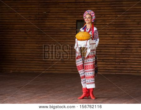 Silver Spring, USA - September 17, 2016: Girl dressed in traditional red Ukrainian embroidered costume clothes dancing with bread at festival on stage
