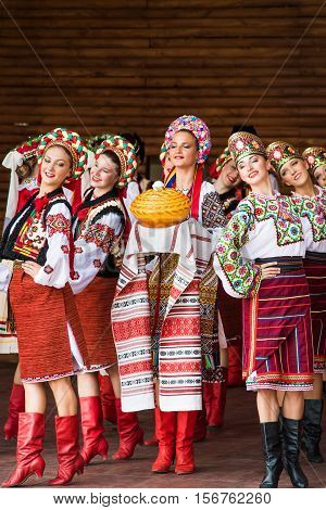 Silver Spring, USA - September 17, 2016: Girls dressed in traditional red Ukrainian embroidered costume clothes dancing with bread at festival on stage