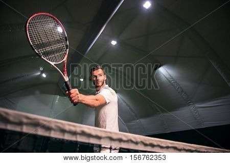 I will be the winner. Low angle of professional handsome bearded tennis player holdign racket and beeing involved in set while training in indoor tennis court