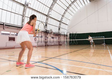 Harsh competition. Professional active players playing tennis in the indoor tennis court while competeing between each other
