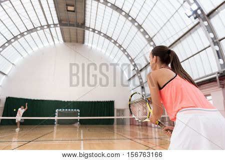 Like doing it. Positive professional tennis players playung tennis while training in indoor tennis court