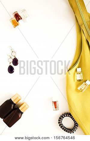 Flat lay for fashion blog and social media. Woman's glamour beauty accessories on a white background. Designer yellow dress jewelry perfumes spiral hair ties. Copy space for text