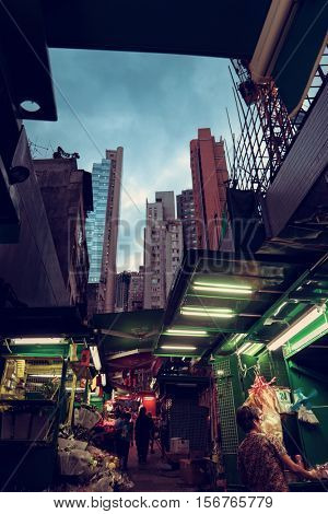 HONG KONG - October 2016: Graham street market. Evening view through stall roofs with skyscrapers in background.