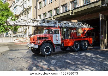 Kiev, Ukraine - May 25, 2013: Ukrainian firetruck driving from station with ladder or crane