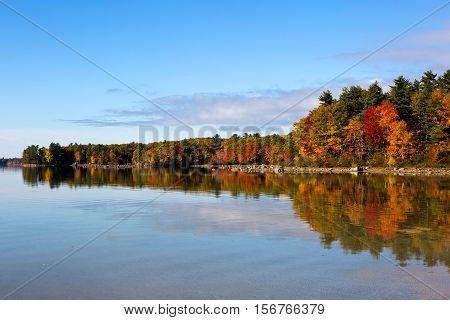 Autumn fall trees reflect colors on Lake Sabago Maine USA.