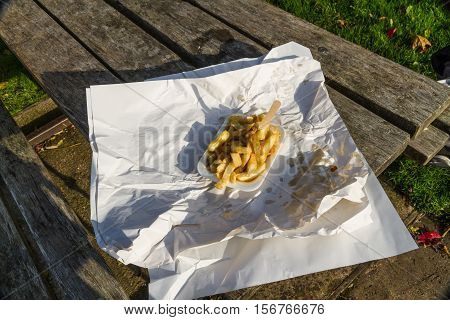 Portion of British chips or fries with wooden fork in carton with wrapping paper on a sunny day.