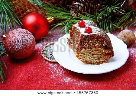 Christmas table setting. Bundt cake pudding sprinkled with sugar powder decorated with red currant.