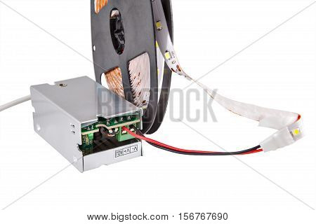 Close-up of LED tape light on the plastic reel connected to a voltage transformer isolated on white background.