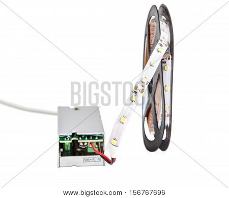 Close-up of LED strip on the plastic coil connected to a voltage converter isolated on white background.