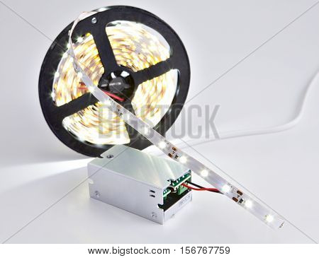 Reel of luminous LED strip light connected to voltage transformer.