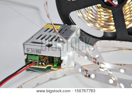Lighted diodes on reel LED tape and voltage converter.