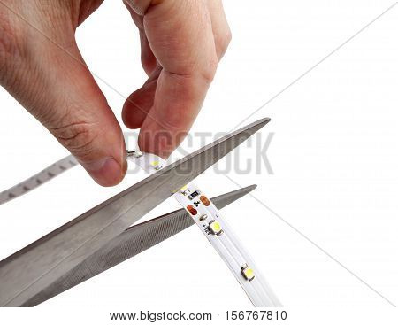 Close-up of hands hold scissors that are cutting LED strip isolated on white background.