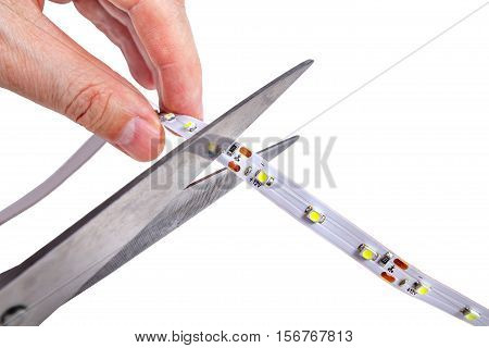 Closeup of hands holding a pair of scissors cut the LED tape isolated on white background.