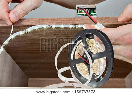 Close-up of hands handyman paste LED tape inside the cabinet.