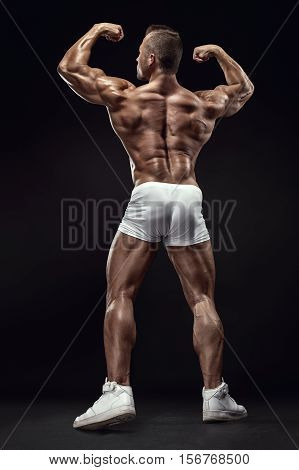 Strong Athletic Man Fitness Model posing back muscles triceps latissimus over black background poster