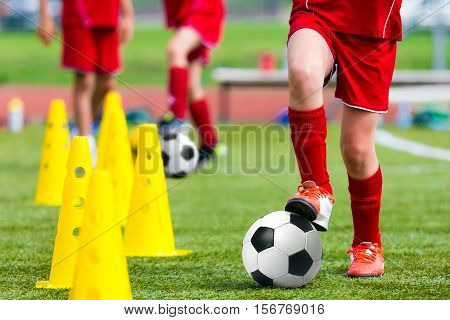 Kids Football Soccer Training.Young Athlete with Football Ball on Pitch. Child in Red Soccer Uniform Kicking Ball. Boy Practice Dribbling Drills on Sport Grass Field