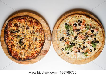 Burnt and normal two pizza with tomatoes, salami, pepperoni on wooden rustic background top view.