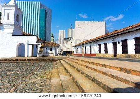 View of the historic La Merced church in Cali Colombia with modern buildings in the background