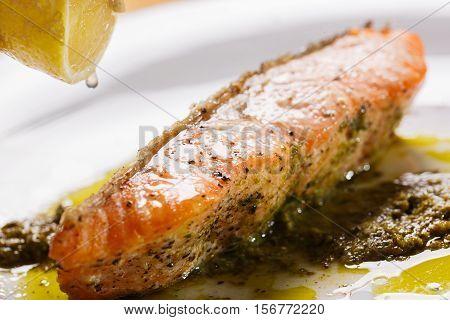 Crisp Salmon Steak with pesto Sauce to top drop lemon.