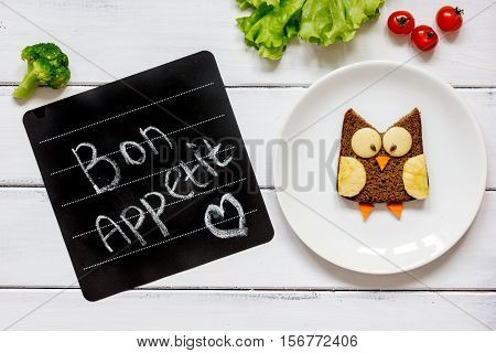 children's breakfast owl shaped sandwich on white plate with vegetables top view at wooden background bon appetit