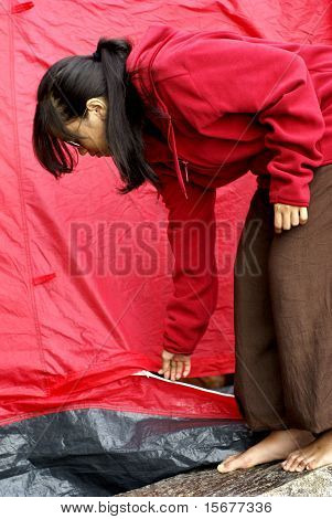 Asian teen girl bent over adjusting red tent