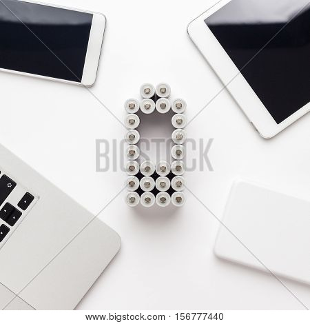 conceptual image of battery charge level pictogram made of rechargeable batteries with some mobile devices like smart phone, tablet computer, laptop and power bank over white background. not isolated