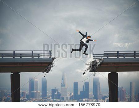 Businessman passes a broken bridge with a big jump