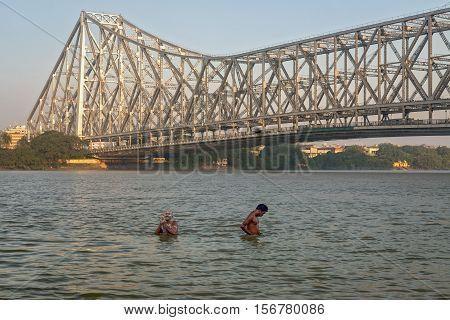 Two unidentified men take a bath in the Ganges river at Mallick ghat Kolkata near Howrah bridge. Photograph taken on November 07, 2016.