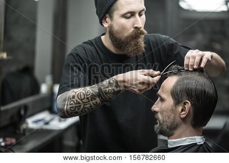 Thoughtful barber with a big beard and a tattoo fixes the hairgrips on the hair of the man in the black hair cutting cape in the barbershop. He wears a black T-shirt with a black cap. Horizontal.