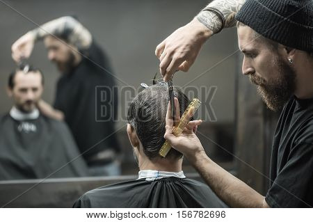 Watchful barber with a beard and a tattoo is cutting the hair of his client in the black cape in the barbershop. He has a hair comb and scissors. They blurry reflected in a mirror. Horizontal.