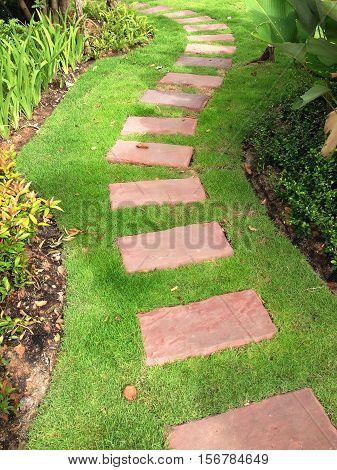 red sand stone pathway on grass in garden