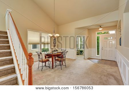 Beige Dining Room Interior With High Ceiling And Staircase