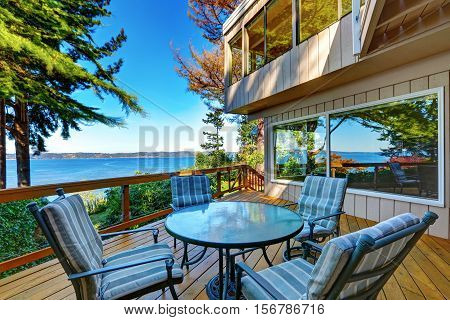 Glass Top Table With Striped Chairs On A Wooden Walkout Deck.