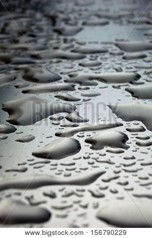 Water droplets on aluminium surface after rainfall. Low angle.