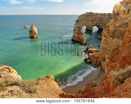 Algarve Portugal. Wild yellow rock cliffs and green-blue ocean.
