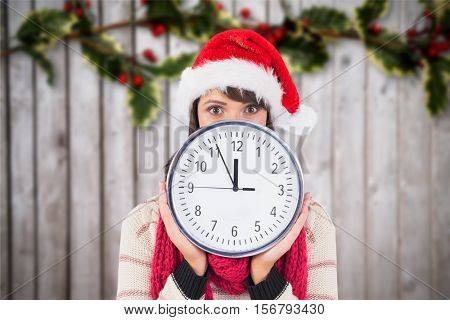 Woman in santa hat holding a wall clock against digitally generated background during christmas time