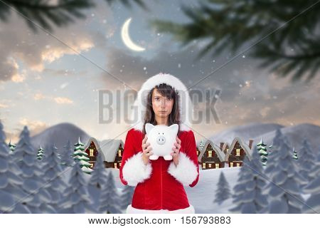 Portrait of sad woman in santa hat holding piggybank during christmas time