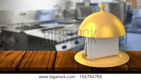 Golden serving platter with card against picture of restaurant kitchen