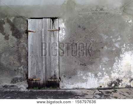 Background concrete wall with old wooden door patina. Detail of an abandoned house. Daylight. Guadeloupe, French West Indies.