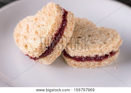 Sweet sandwiches cut in heart shape with red plum jam for Valentine's day