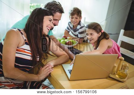 Family using laptop at dinning table in the house