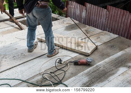 Builder worker man installing cement floor slab panel at building construction site poster