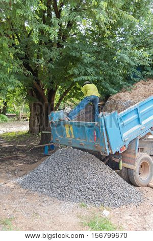 Dumper truck unloading soil or sand at construction site