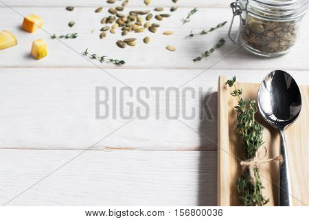 Spoon on board, void, white wood background. Top view on table with pumpkin seed, mockup for any meal. Seasonal menu concept